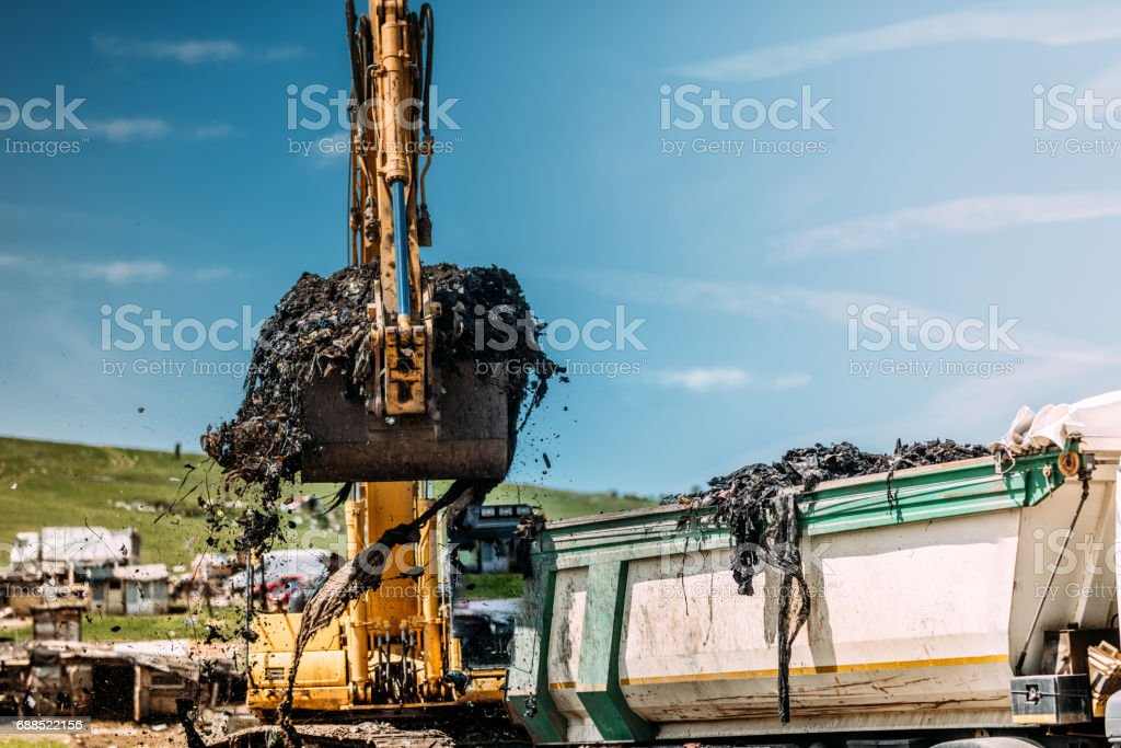 Industrial excavator loading dumper trucks with garbage on site stock photo