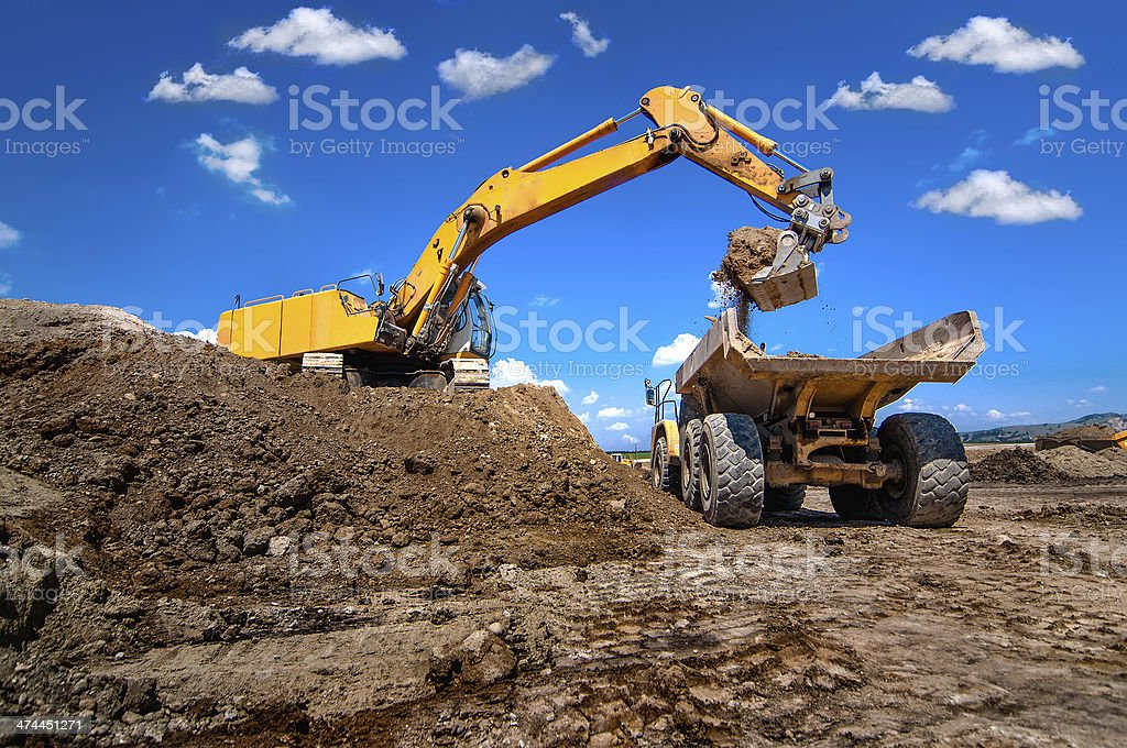 industrial excavator loading soil from sandpit stock photo