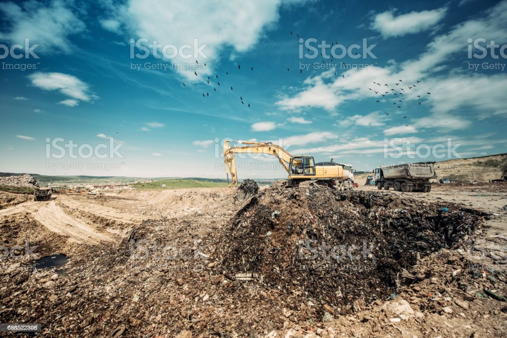 industrial excavator using heavy duty scoop for construction works at garbage dumpsite stock photo
