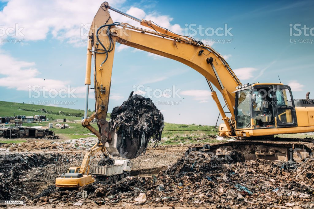Industrial excavators and heavy duty machinery working on garbage dump site. stock photo