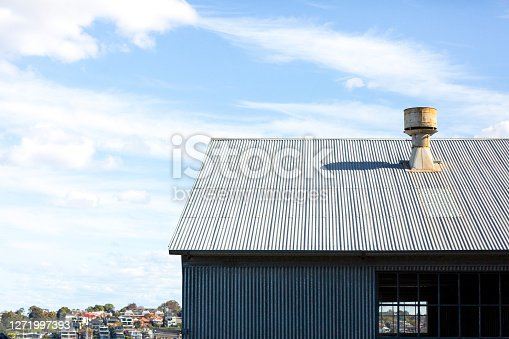 Industrial exterior of abandoned factory with the view of town, sky background with copy space, full frame horizontal composition