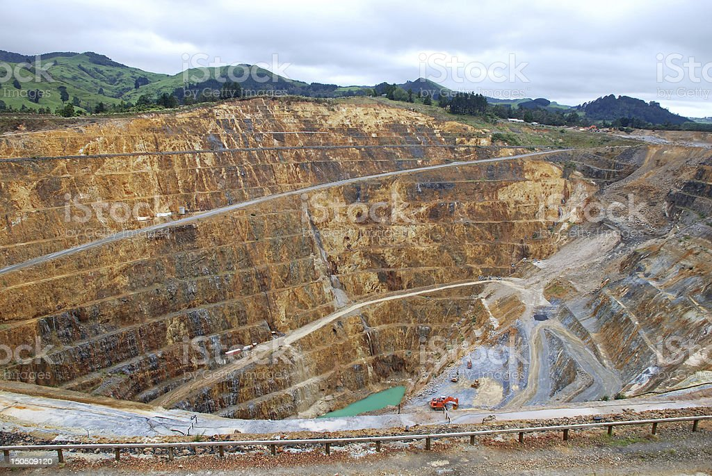 Industrial gold mine surrounded by green hills stock photo