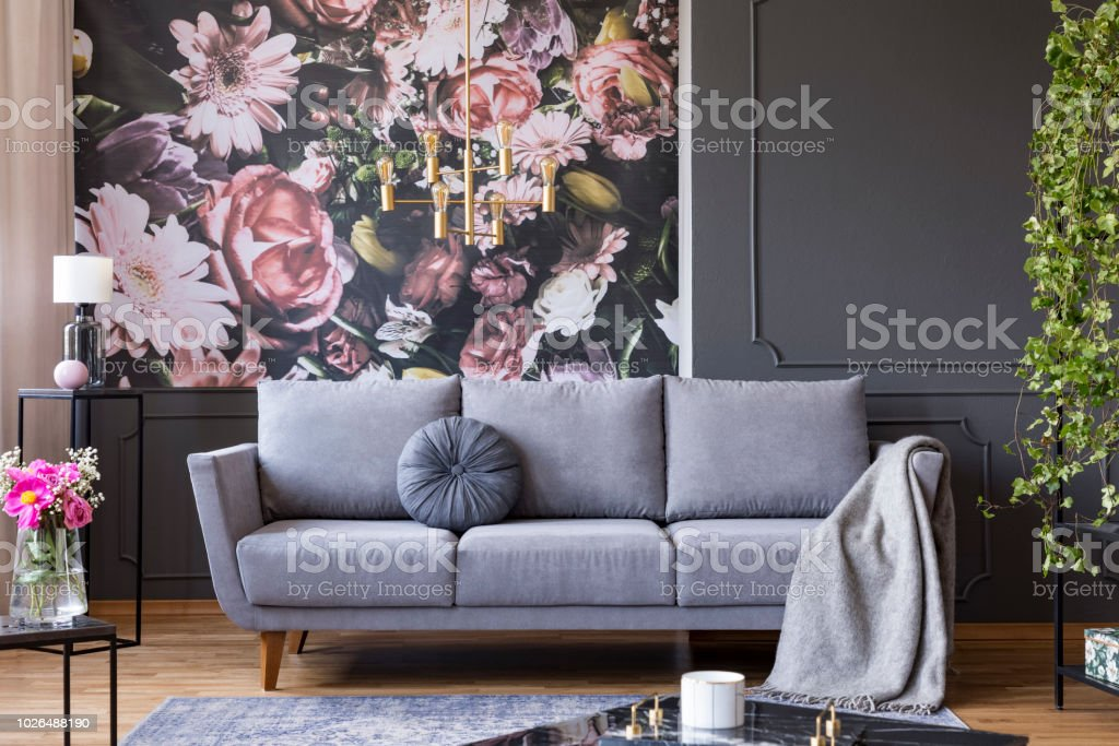 Industrial golden pendant light and black furniture in a dark living room interior with floral wallpaper and a gray couch – zdjęcie