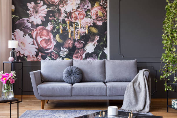 Industrial golden pendant light and black furniture in a dark living room interior with floral wallpaper and a gray couch - foto stock