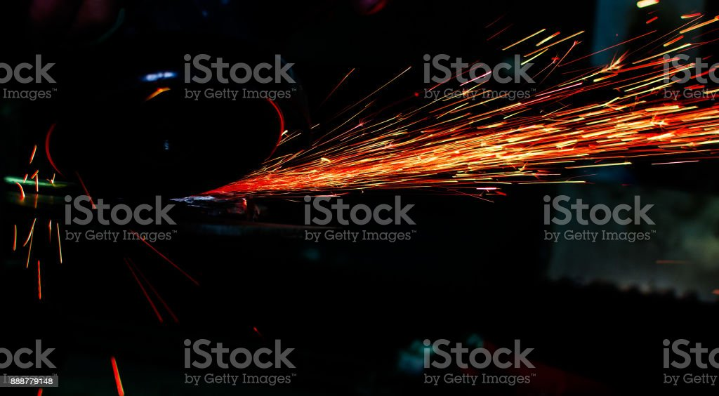 Industrial grinder showers sparks while working with metal.