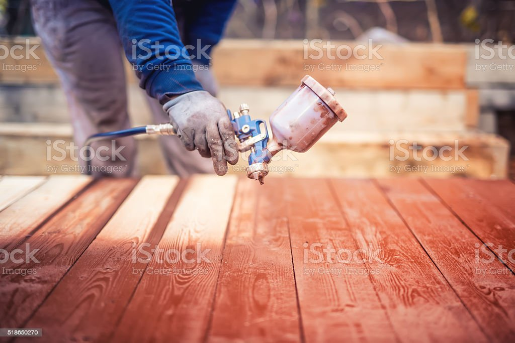 Industrial handyman, construction worker painting with spray stock photo