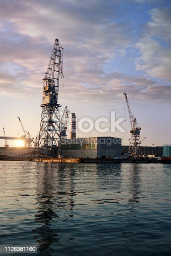 Industrial harbor with cranes at dawn: shipping and naval industry concept