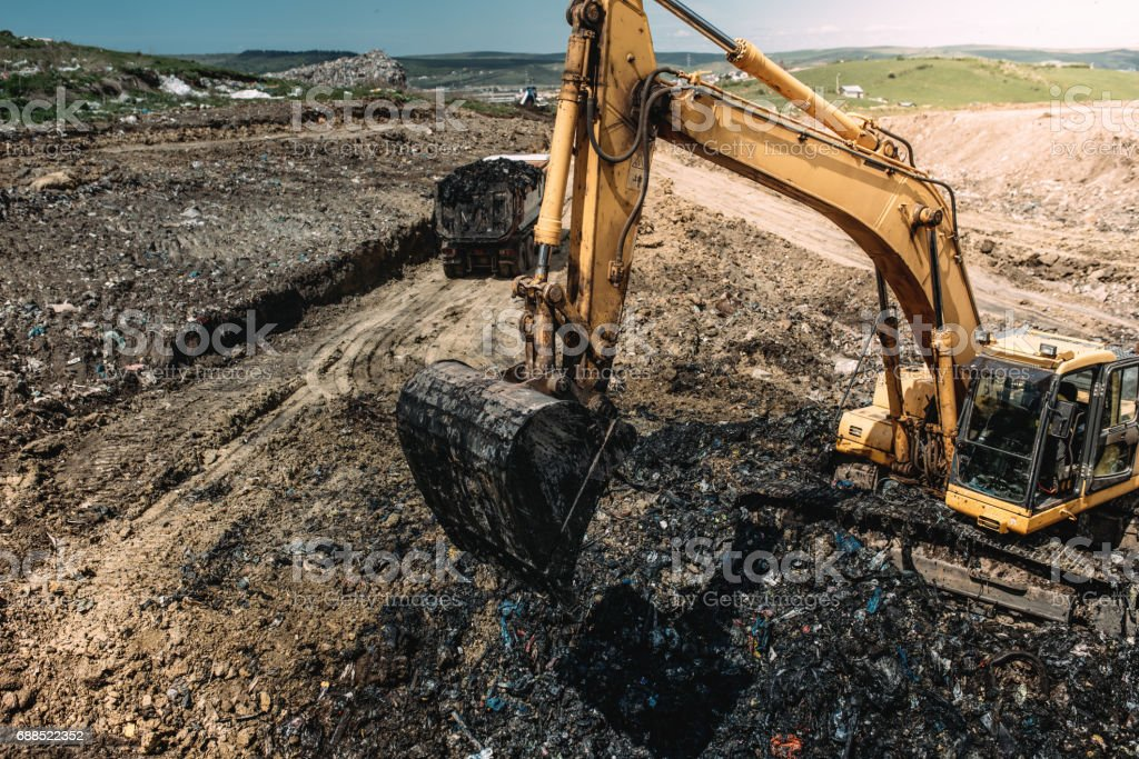 Industrial heavy duty machinery, excavator digging hole and loading garbage into dumper trucks stock photo