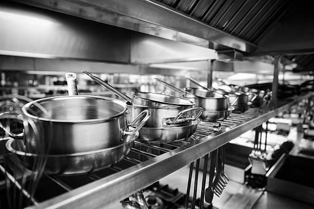 Industrielle Küche mit Töpfen und Werkzeuge auf den Regalen – Foto