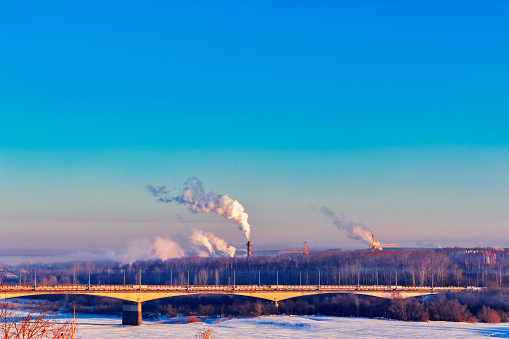 industrial landscape with a bridge over the river in winter
