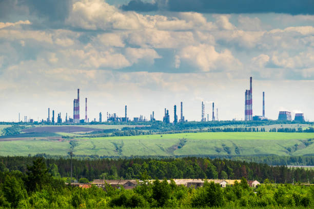 Industrial landscape with an oil refinery on the green hill stock photo