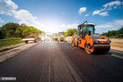 industrial landscape with rollers that rolls a new asphalt in the roadway. Repair, complicated transport movement.