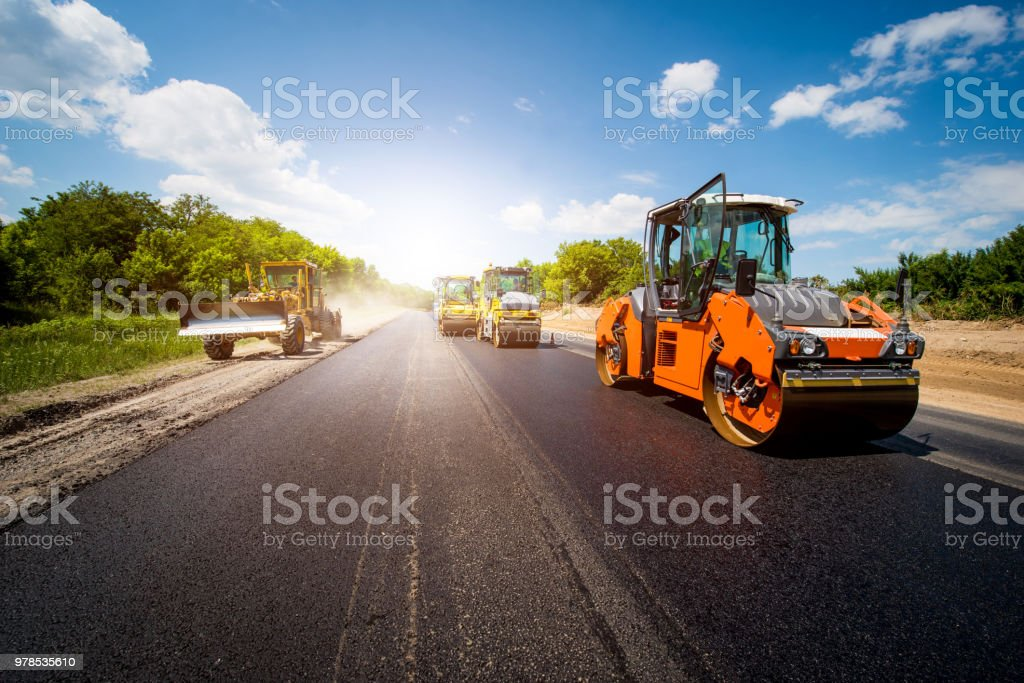 industrial landscape with rollers that rolls a new asphalt in the roadway. Repair, complicated transport movement. stock photo