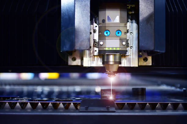 Industrial laser cut machine while cutting the sheet metal industrial Industrial laser cut machine while cutting the sheet metal with the sparking light. laser stock pictures, royalty-free photos & images