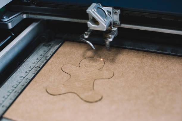 industrial laser gravure un biscuit de noël pain d'épice mignon sur un carton - objet gravé photos et images de collection