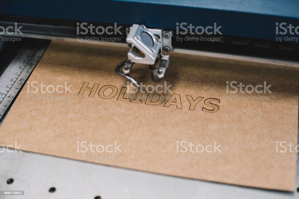 産業レーザー プロセス、段ボールで「休日」の言葉を彫刻 ストックフォト