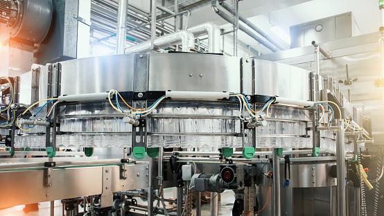 Industrial machine conveyor with plastic bottles in beverage factory, industry equipment.
