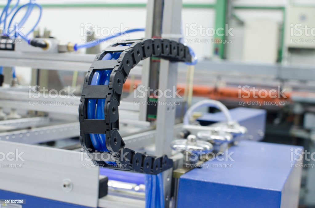 Industrial machine flexible power trak wire tray moving mechanism detail, selective focus copyspace background stock photo