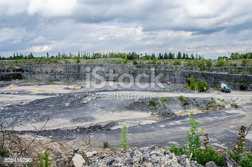 Industrial machinery at work in a stone-pit quarry during summer day