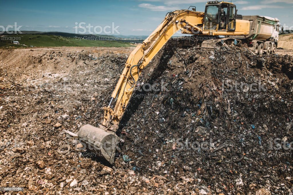 Industrial machinery excavating garbage. Close up of heavy duty excavator using scoop and working stock photo