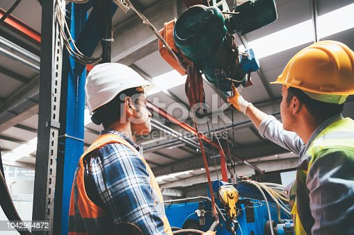 Skilled Industry worker and manager man using overhead crane controller and pushing button while managing crane at industrial tractor plant shop