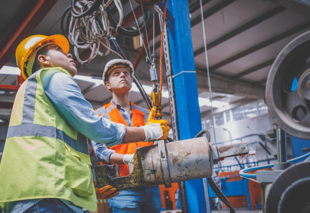 Industrial machinery male employees working with remote control for operating crane stock photo