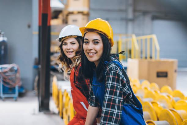 empleado maquinaria industrial dos mujeres en almacén de la fábrica - suministros escolares fotografías e imágenes de stock