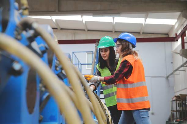maquinaria industrial dos trabajadoras trabajadoras en almacén de fábricas - suministros escolares fotografías e imágenes de stock