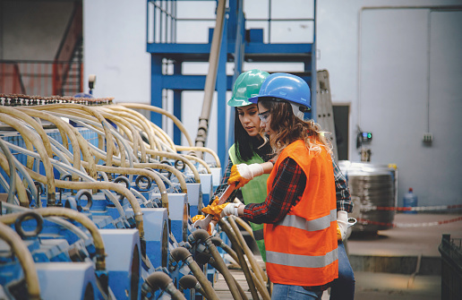 Portrait of trainee mechanic professional young female technical engineer and businesswoman with helmet checking and repairing industry milling machining with big wrenches tool in a large shipping manufacturing facility warehouse at metal cable factory XXXL
