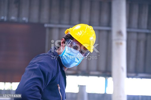 Caucasian Industrial man works with a face mask. Safety for work concept. Close up composition.
