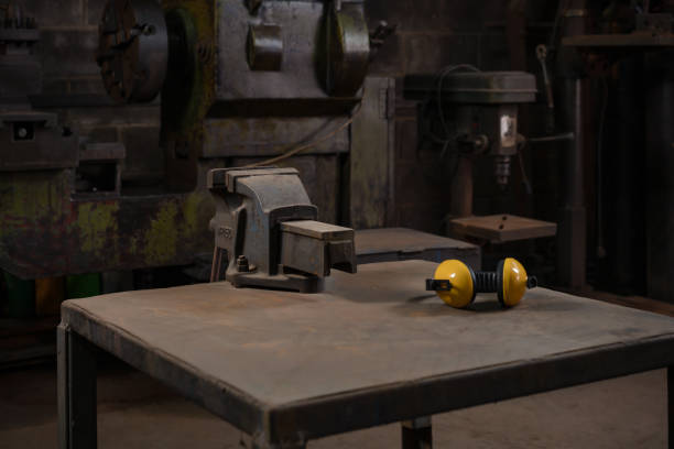 Industrial mechanical cast iron vice bolted to a metal work station table in a dark traditional old style repair workshop next to yellow ear defenders dark workshop with a workbench and iron vice with ear defenders workbench stock pictures, royalty-free photos & images