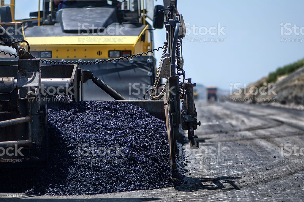 Industrial pavement machine laying fresh asphalt on highway stock photo