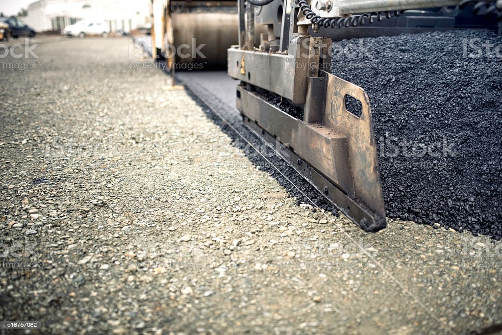 industrial pavement truck laying fresh asphalt, bitumen during road works stock photo