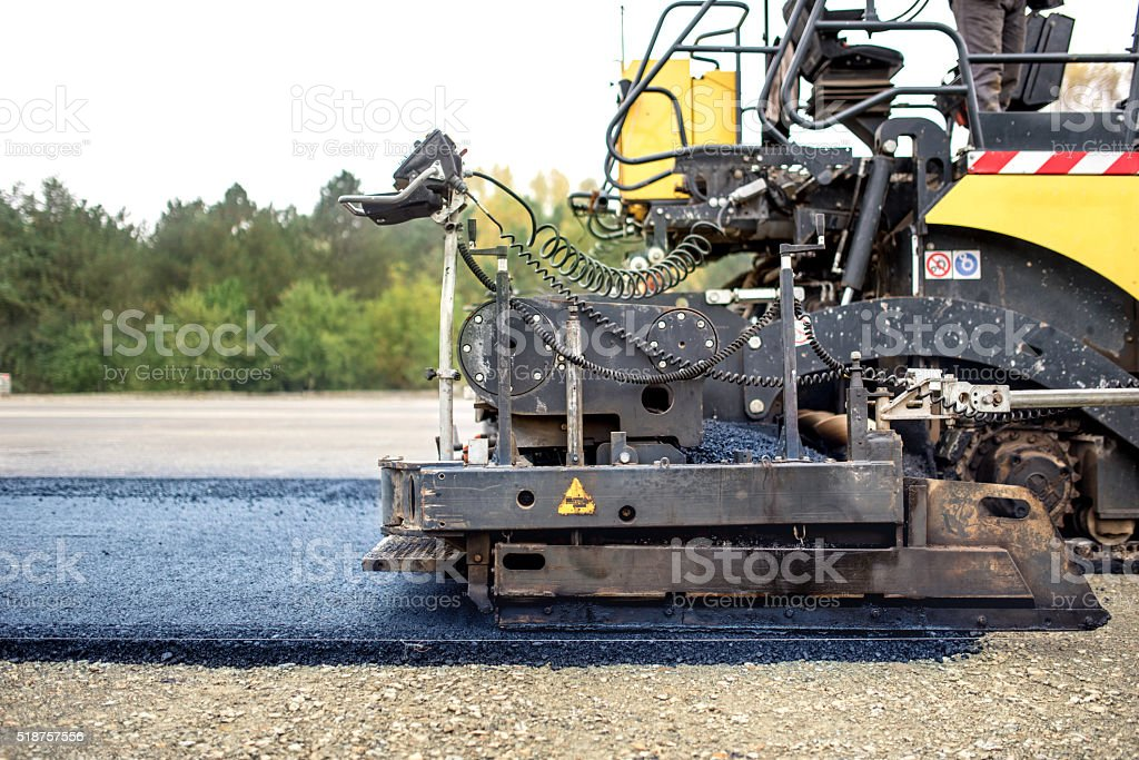 industrial pavement truck laying fresh asphalt on construction site, asphalting stock photo