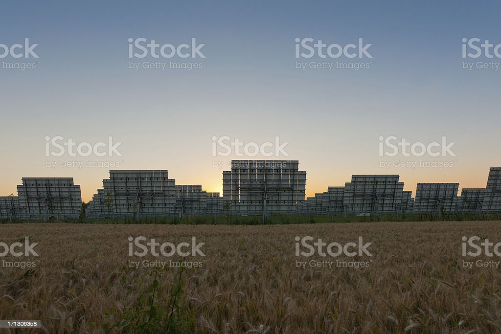 Industrial photovoltaic panels, from behind, near a wheat field, Piedmont stock photo