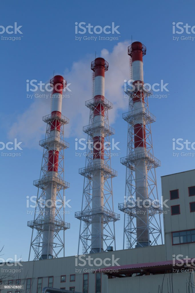Industrial pipe thermal power station white with red from the smoke in the blue sky stock photo