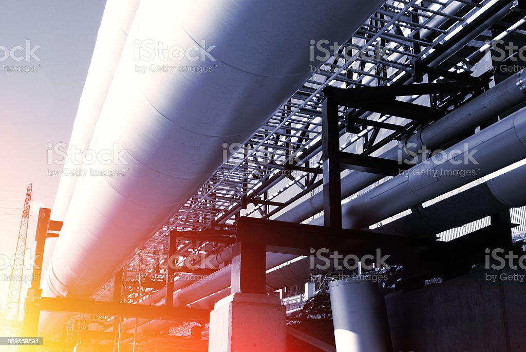industrial pipelines on pipe-bridge against blue sky stock photo