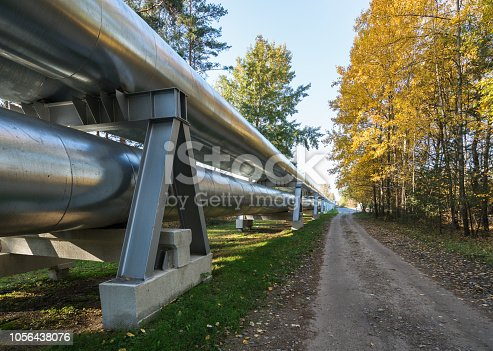 Industrial pipelines on pipe-bridge against blue sky