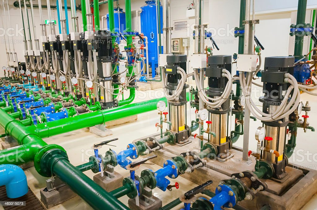 Industrial piping of different colors inside a warehouse stock photo