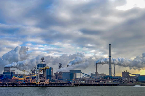 Industrial plant with big smoke stacks,  in the foreground water stock photo