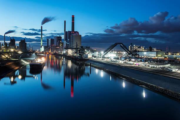 industrial plants in the distance at night - industriegebied stockfoto's en -beelden