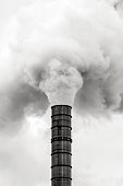 Industrial pollution, smoke from factory stack, black and white, background with copy space, full frame vertical composition