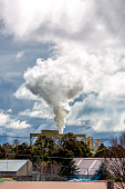 Industrial pollution, smoke from factory stacks over town, background with copy space, full frame vertical composition