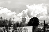 Industrial pollution, smoke from factory stacks over town, black and white, background with copy space, full frame horizontal composition