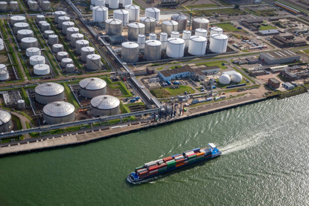 Industrial port with oil silo farm and container ship stock photo