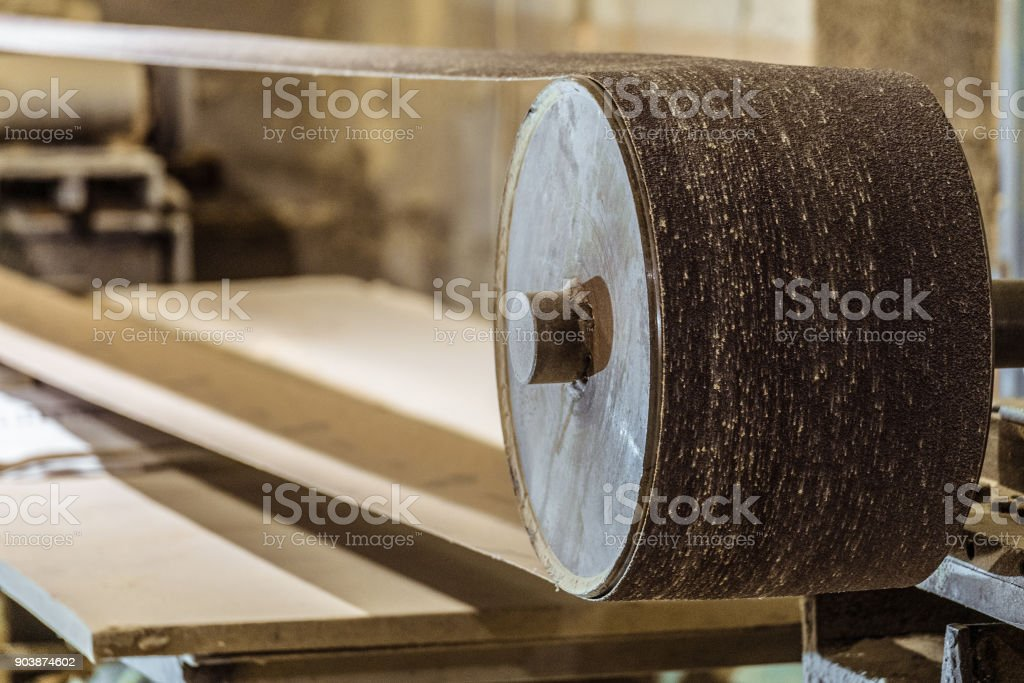 Industrial professional abrasive sanding machine with grinding belt close-up. Mechanized woodworking carpenter tool in carpentry workshop. Selective focus. stock photo