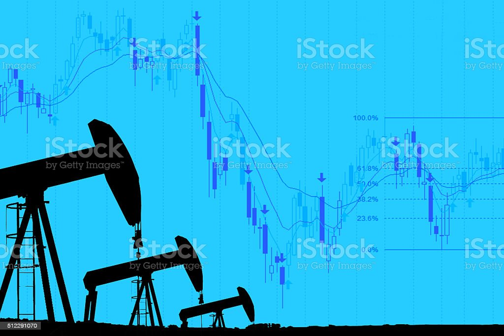 industrial pump jack and falling oil graph on blue background stock photo