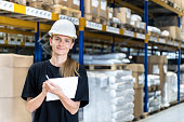 Horizontal color portrait of young beautiful female manual worker or quality controller smiling at camera in distribution storage compartment. Industrial laborer writing notes, wearing black protective workwear t-shirt and white hardhat. Blond woman looking happy and confident. Large distribution warehouse in background with racks full of packages, boxes, pallets, crates ready to be delivered. Logistics, freight, shipping, receiving.