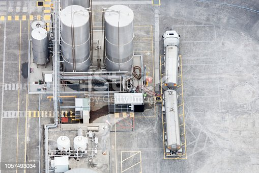 Industrial refinery depot with trucks waiting.