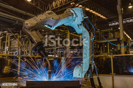 693576566 istock photo Industrial robot is welding assembly automotive part in car factory 908255484